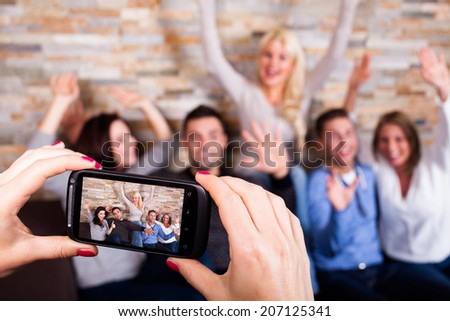 woman taking a photo with her smartphone of their friends - stock photo