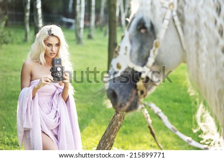 Woman taking a picture of a white horse - stock photo