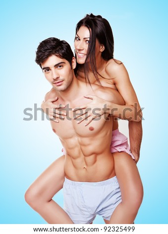 Woman Taking A Piggyback Ride on the back of a fit handsome young man, three quarter studio portrait on blue - stock photo