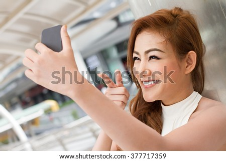 woman taking a selfie with her smartphone, pointing up to the camera