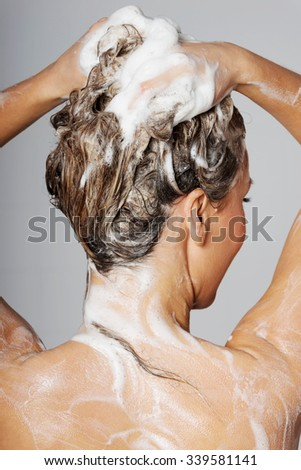 Woman taking a shower and shampooing her hair - stock photo
