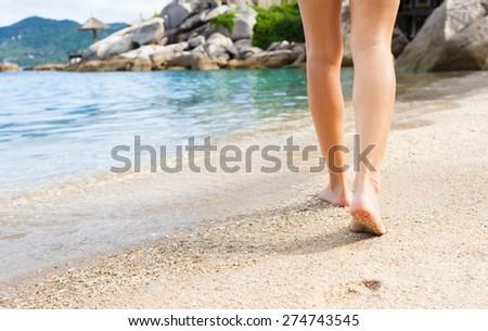 Woman taking a walk down a beautiful beach.  - stock photo