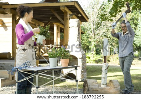 woman taking care of plant and man chopping firewood