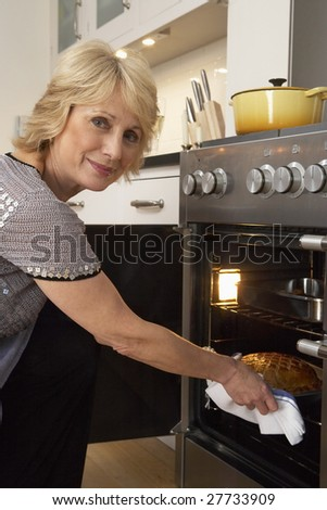 Woman Taking Food Out Of The Oven