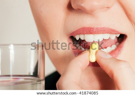 Woman taking in a pill (close up on mouth)