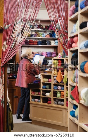 Woman taking inventory in yarn shop - stock photo