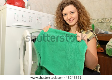 woman taking linen from washing machine - stock photo