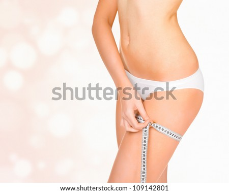 Woman taking measurements of her body, abstract background with circles and copyspace - stock photo