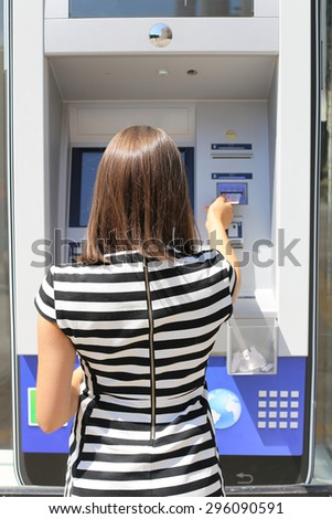woman taking money with credit cart from ATM - stock photo