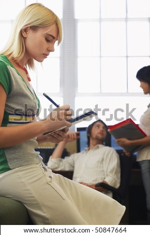 Woman taking notes with man and woman talking in background. - stock photo