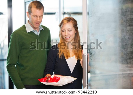 Woman taking out product from freezer while shopping with husband - stock photo