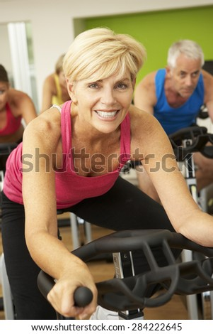 Woman Taking Part In Spinning Class In Gym - stock photo