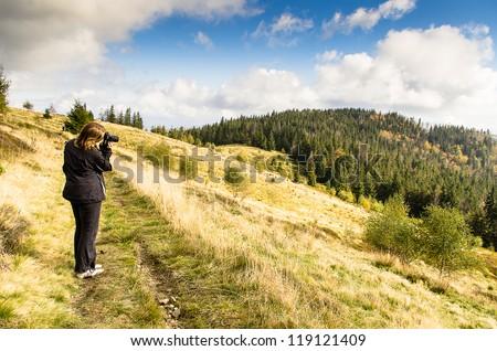 woman taking photo during mountain trip,beauyfull landscape - stock photo