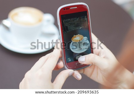 Woman taking photo of cup of coffee on her smartphone for social networks - stock photo