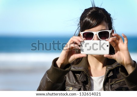Woman taking photo with cellphone on the beach on spring. Happy girl on vacation taking picture on sea background. - stock photo