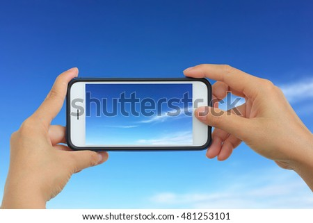 Woman Taking photo with mobile phone, Cellphone on blurred background on clouds in the blue sky