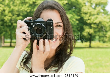 Woman taking photo with old fashioned camera.