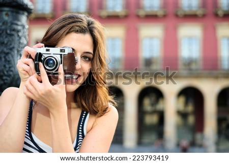 Woman taking photo with retro camera in Gijon Main Square, Asturias, Spain. Female tourist visiting typical spanish landmark on summer vacation travel. - stock photo