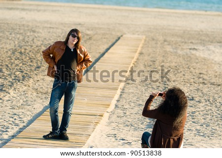 Woman taking photographs of a teenager on the beach - stock photo