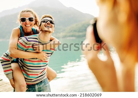 Woman taking picture at friends - stock photo