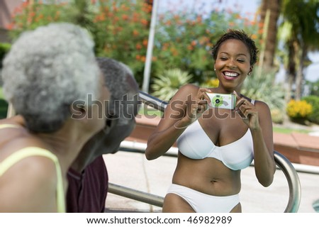 Woman Taking Picture at Poolside Barbecue - stock photo