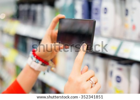 Woman taking picture in supermarket  - stock photo