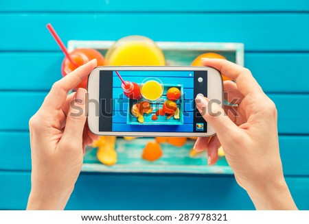 woman taking picture of vintage tray with fruits on her smartphone. Top view - stock photo