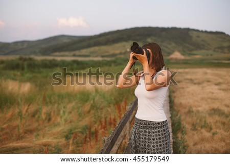 woman taking picture with camera outdoor - stock photo