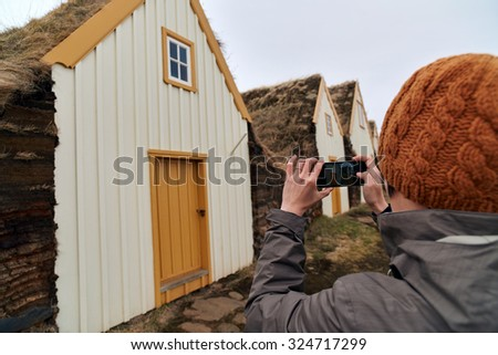 Woman taking picture with mobile cell phone of Traditional Icelandic Turf Houses in North Iceland - stock photo