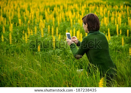 Woman taking pictures to flowers with a cellphone - stock photo