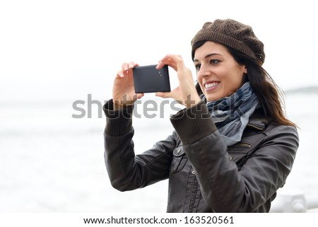 Woman taking pictures with black cellphone. Cheerful brunette using phone camera. - stock photo