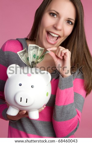 Woman taking piggy bank money - stock photo