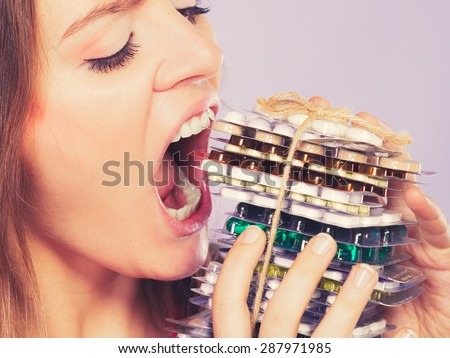 Woman taking pills. Girl female eating stack of tablets. Drug addict and health care concept. Overdose. - stock photo