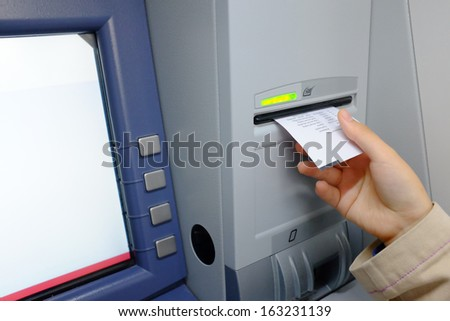 Woman taking receipt from an ATM - stock photo