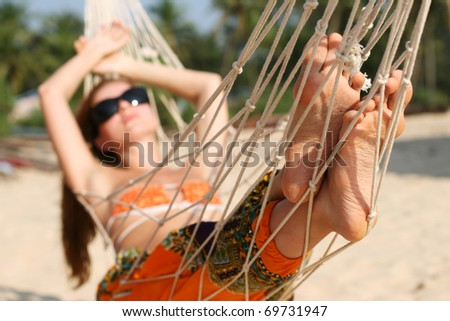 Woman taking sunbath in hammock on the beach - stock photo