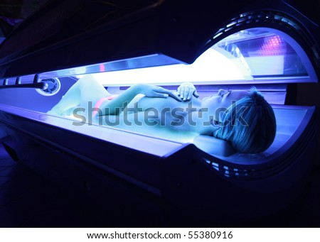 woman taking sunbath in sunbed - stock photo