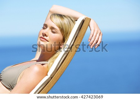 woman taking sunbath near swimming pool and beach - stock photo
