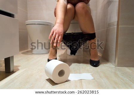 Woman taking the role of soil in a toilet - stock photo