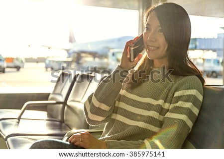 Woman talk to mobile phone at airport