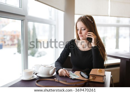 Woman talking by the phone while waiting for a waiter - stock photo