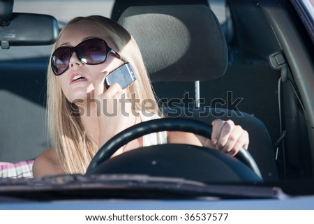 Woman talking in the car by mobile - stock photo