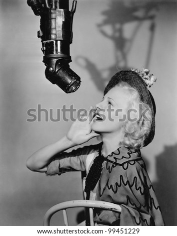 Woman talking into boom mike - stock photo