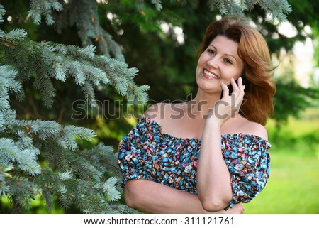 Woman talking on a cell phone in the park - stock photo