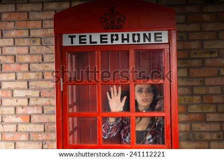 Woman talking on a telephone peering out of a phone booth in horror as she notices something terrible taking place outside - stock photo