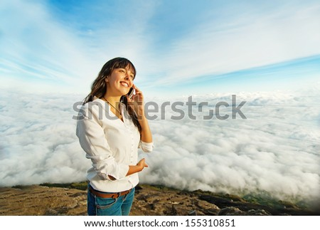 woman talking on mobile phone in the clouds - stock photo