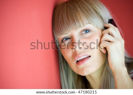Woman talking on mobile phone over red background - stock photo