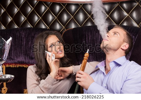 woman talking on phone and resting in Arabic cafe. man and woman smoking hookah and looking - stock photo