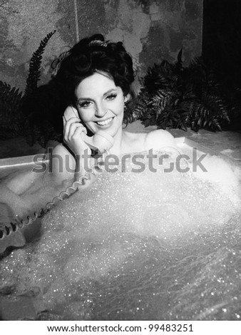Woman talking on phone in bubble bath - stock photo