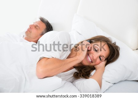 Woman Talking On Phone While Man Sleeping On Bed - stock photo