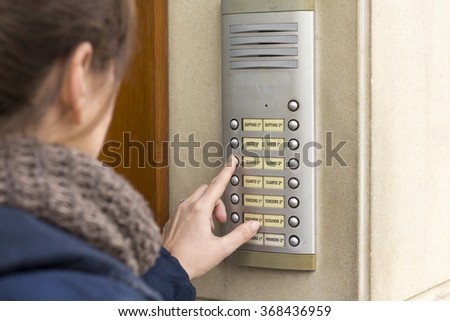 Woman talking on the intercom and presses the button - stock photo
